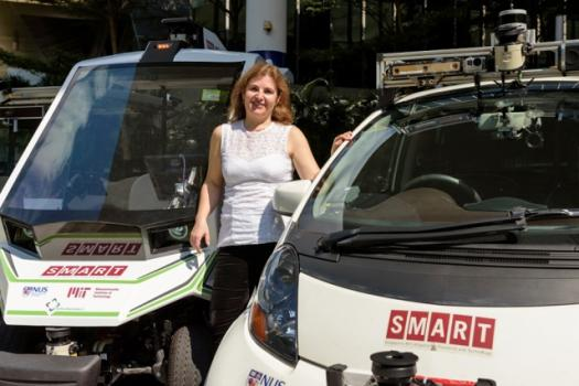 Professor Daniela Rus stands with autonomous SMART vehicles on the MIT campus.