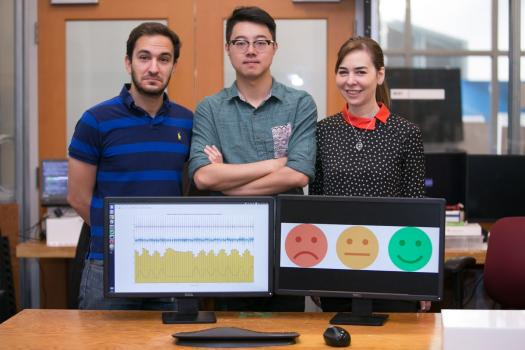 Left to right: PhD student Fadel Adib, PhD student Mingmin Zhao, and Professor Dina Katabi pose with their EQ-Radio device, which can detect emotion using wireless signals.