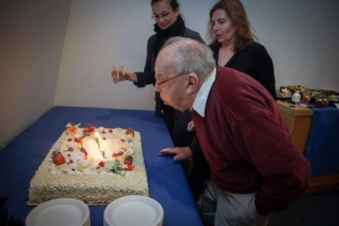 Professor Emeritus Fano blows out the candles with CSAIL Director Daniela Rus (right) and Event Coordinator Victoria Palay.